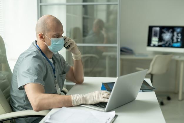 Вид сбоку на лысого зрелого мужчину-клинициста в защитной маске, сидящего за столом перед ноутбуком в медицинском кабинете и разговаривающего по мобильному телефону Premium Фотографии