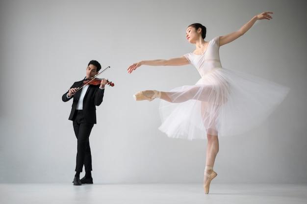 Вид сбоку балерина танцует и музыкант скрипки