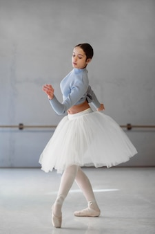 Балерина танцует в юбке-пачке и пуантах, вид сбоку