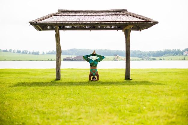 夏の日に公園で逆立ちをしている裸足の若い集中女性の側面図