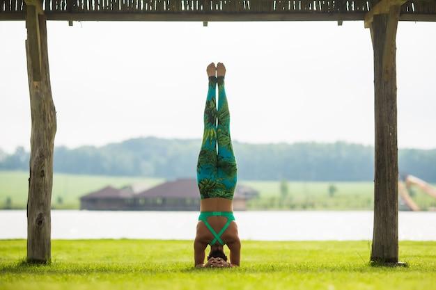 Вид сбоку босоногой молодой сосредоточенной женщины, делающей стойку на руках в парке в летний день