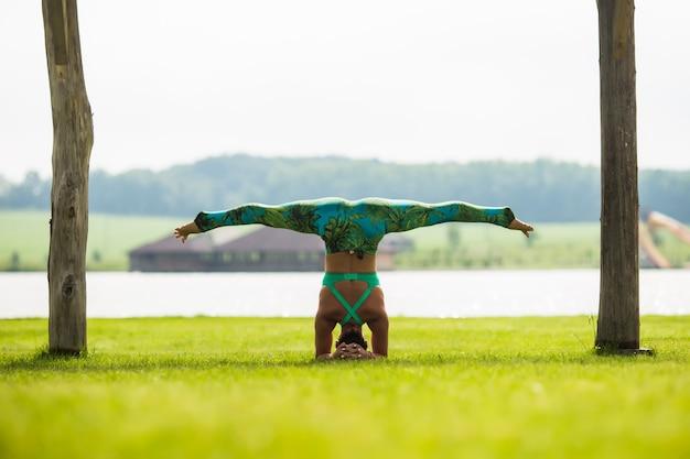 여름 날에 공원에서 물구나무 서기를하고 맨발의 젊은 집중된 여자의 측면보기
