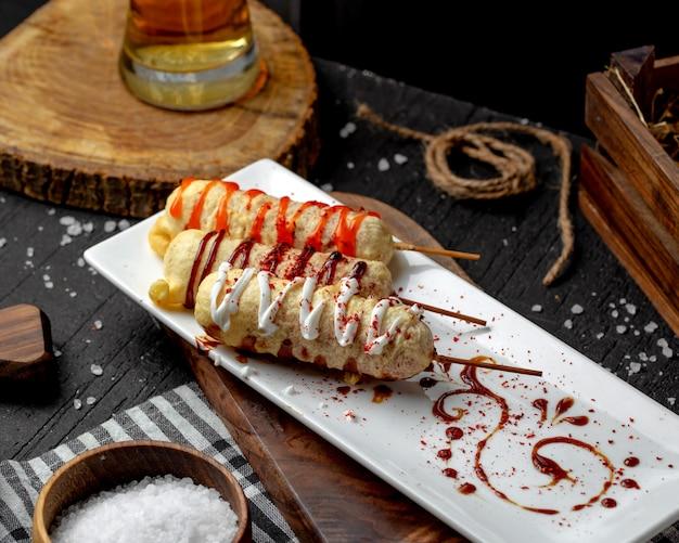 Вид сбоку побитой колбасы на деревянных палочках с соусом на тарелке