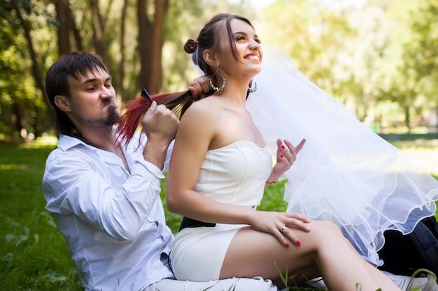 笑顔の美しい花嫁の髪をとかすひげを生やした新郎の側面図。結婚式の後に屋外で楽しんでいる愛らしい幸せな新婚夫婦。結婚式、愛とケアの概念。
