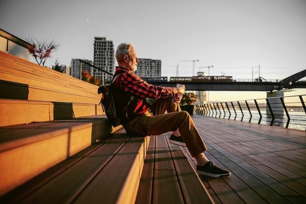 Вид сбоку бородатого хипстера старшего человека, сидящего на лестнице на открытом воздухе, пить кофе.