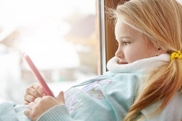 ウィンドウに座っている美しい金髪少女の側面図