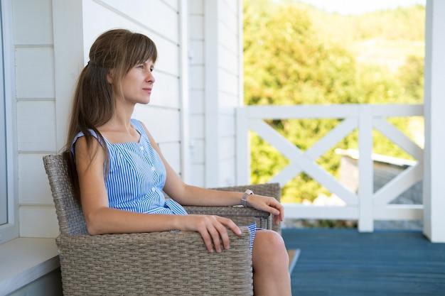 니트의 자에 앉아 파란 드레스에 아름 다운 갈색 머리 여자의 측면 보기. 발코니에서 신선한 공기를 마시며 휴식을 취하는 개념.