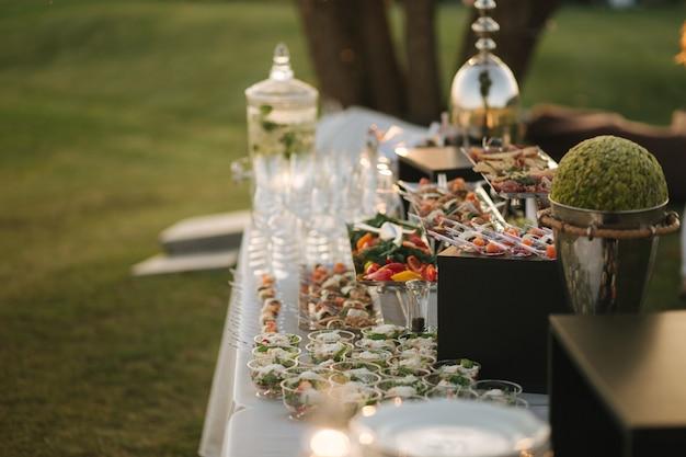 여름에 식탁에서 제공되는 일몰의 맛있는 샐러드와 스낵으로 야외에서 아름다운 케이터링을 하는 모습