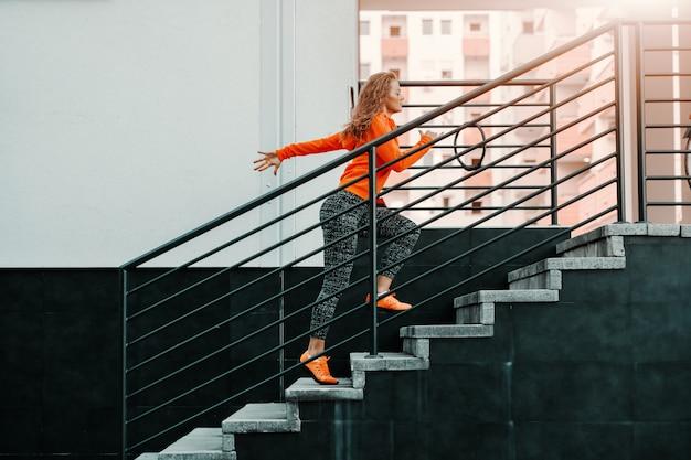 階段の上を実行しているスポーツウェアで美しいフィットスポーティな白人女性の側面図です。