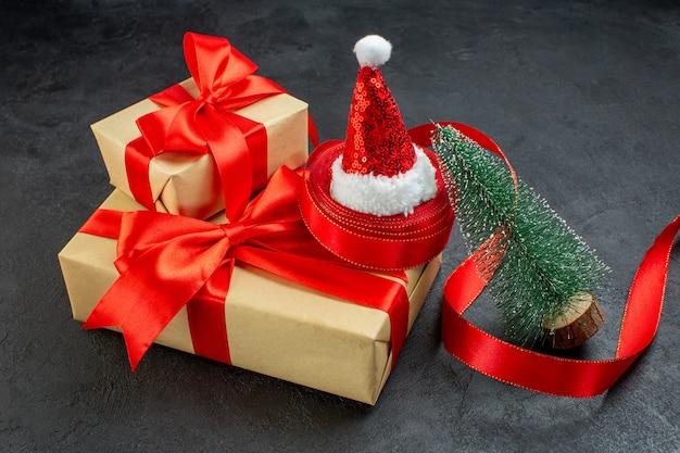 Вид сбоку красивых подарков с красной лентой и новогодней елкой в шляпе санта-клауса на темном столе