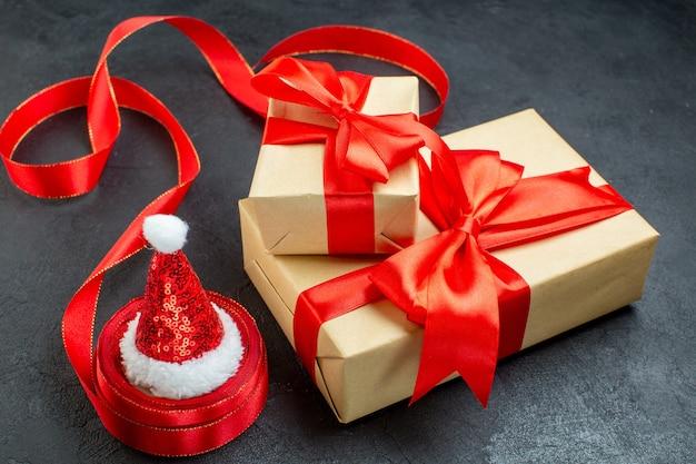 Вид сбоку красивых подарков с красной лентой и шляпой санта-клауса на темном столе