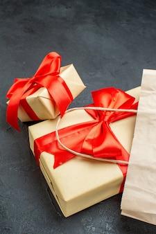 Вид сбоку красивых подарков с красной лентой на темном столе