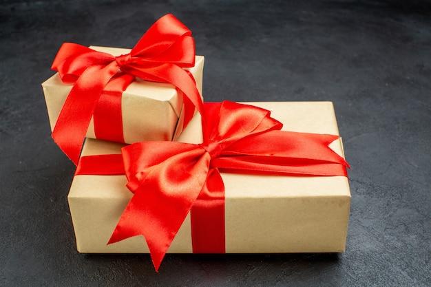 Вид сбоку красивых подарков с красной лентой на темном фоне