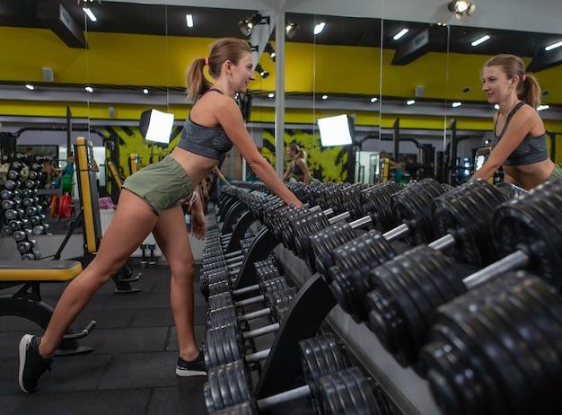 笑顔で鏡を見て、ジムのラックで重いダンベルを持ち上げるスポーツウェアの美しい女性の側面図