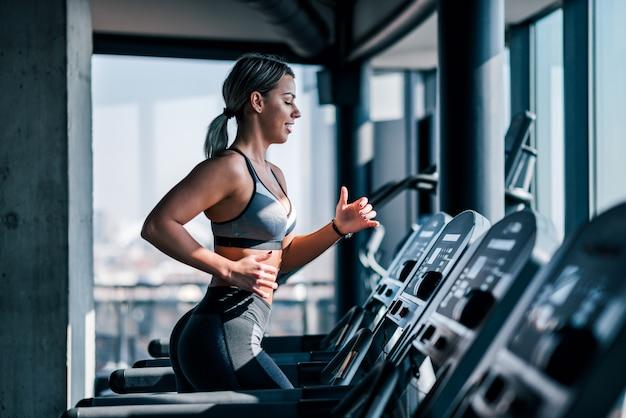 トレッドミルで実行されている美しい筋肉の女性の側面図です。