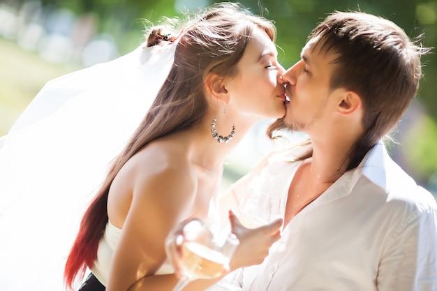 優しいキスを共有し、シャンパンのグラスを保持している美しい新婚夫婦の側面図
