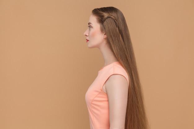 Вид сбоку красивой серьезной женщины с длинными каштановыми волосами