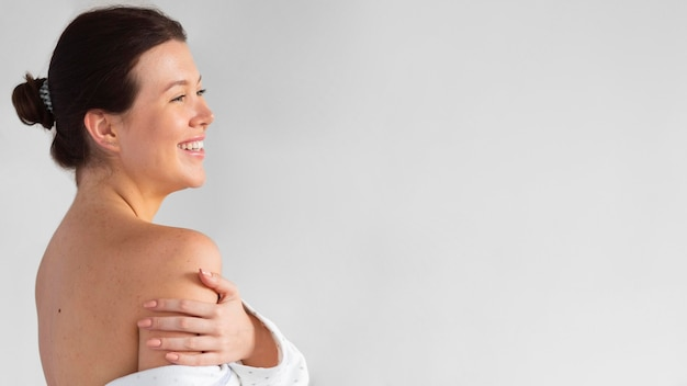 Вид сбоку красивой улыбающейся женщины, занимающейся самообслуживанием
