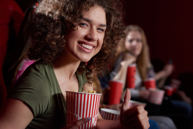 おいしいポップコーンを保持している映画館ホールを見てボリュームの巻き毛の笑顔美人の側面図です。現代の映画館で面白い映画を見て感情的にブルネットの少女。