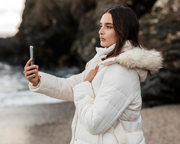 スマートフォンで写真を撮るビーチで美しい女性の側面図