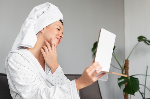 Вид сбоку красивой женщины, смотрящей в зеркало, занимаясь самообслуживанием