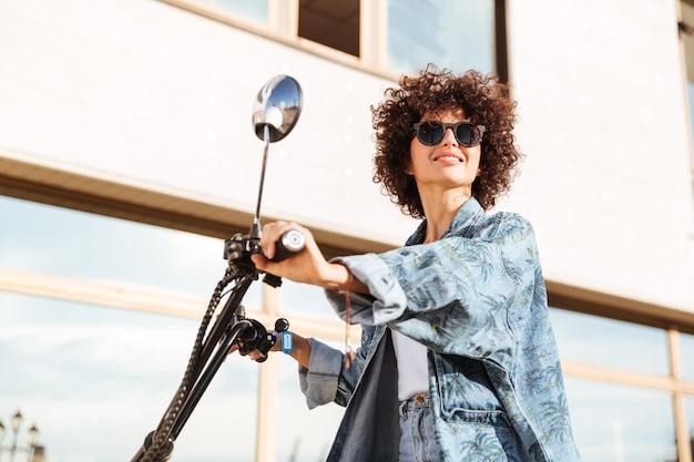 Взгляд со стороны красоты усмехаясь курчавой женщины в солнечных очках сидя на современном мотобайке outdoors и смотря прочь