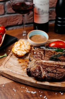 쇠고기 스테이크의 측면보기 나무 보드에 구운 야채와 바베큐 소스와 함께 제공