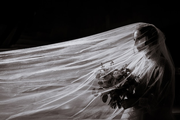 Черно-белое фото невесты с букетом в руках и длинной фатой, вид сбоку
