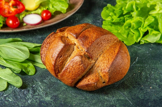 Вид сбоку свежих нарезанных овощей черного хлеба на тарелке и метров зеленой пачки на поверхности темных цветов