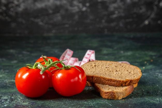 暗い色の背景に茎とメーターで新鮮なトマトをスライスする黒パンの側面図
