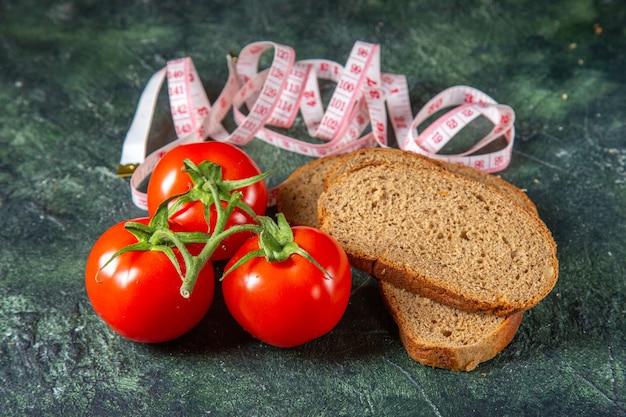 黒パンの側面図は、暗い色の表面に茎とメーターで新鮮なトマトをスライスします