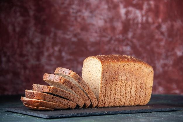 混合色の苦しめられた背景の上の黒い板上の黒いパンのスライスの側面図