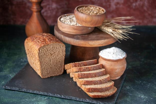 黒のトレイに黒パンのスライスと栗色の背景に茶色のボウルに小麦粉の側面図