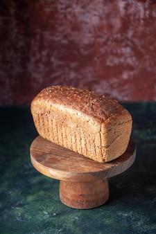 空きスペースと混合色の苦しめられた背景に木の板の黒いパンのスライスの側面図