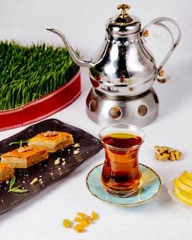 Вид сбоку черного чая в бокале armudu с пахлавой