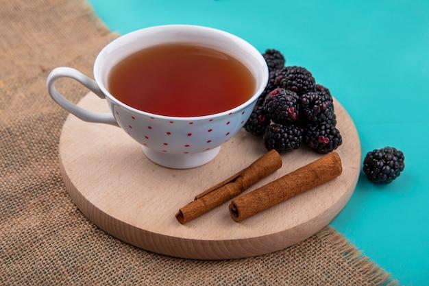Вид сбоку ежевики с чашкой чая и корицей на подставке на бирюзовой поверхности