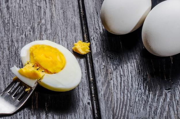 Взгляд со стороны вареного яйца половинного с вилкой на деревянной деревенской