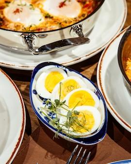 テーブルの上のボウルにゆで卵の側面図