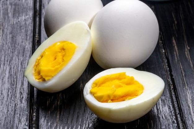 Вид сбоку вареных яиц на деревянный деревенский