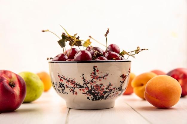 Вид сбоку чаши вишни с рисунком фруктов как персик и груша на деревянной поверхности и белом фоне