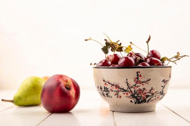 Вид сбоку чаши вишни с персиком и грушей на деревянной поверхности и белом фоне