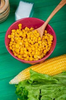 緑のテーブルにトウモロコシレタス塩とトウモロコシ種子のボウルの側面図