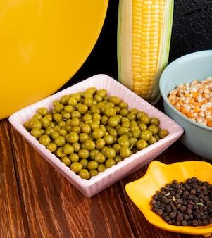Вид сбоку миски семян зеленого гороха кукурузы и черного перца на деревянный стол