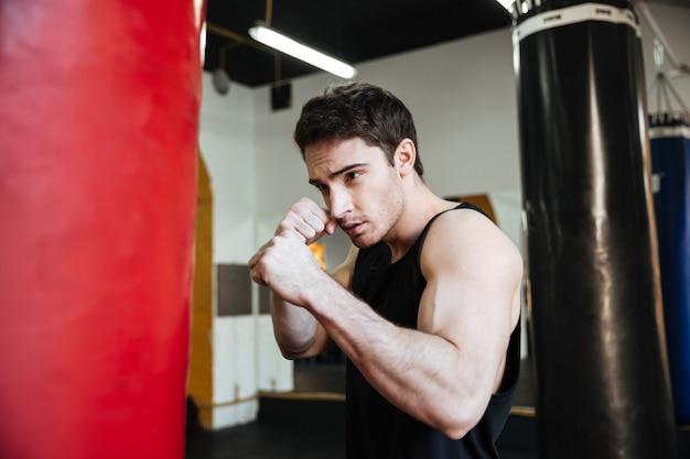 Вид сбоку тренировки боксера с грушей
