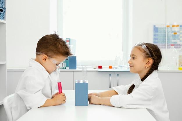 안전 안경 실험실에서 소년과 소녀 과학자의 측면보기