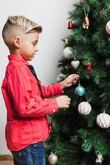 크리스마스 트리를 장식하는 소년의 모습