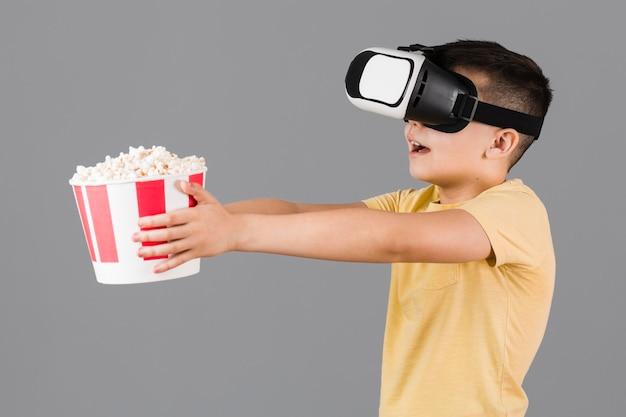 Взгляд со стороны мальчика держа попкорн и нося шлемофон виртуальной реальности
