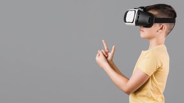 Вид сбоку мальчика, играющего с гарнитурой виртуальной реальности