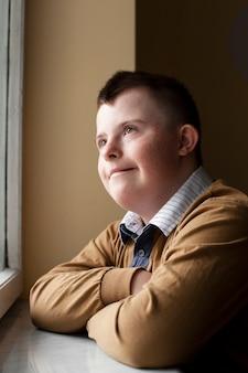 Вид сбоку мальчика с синдромом дауна позирует у окна