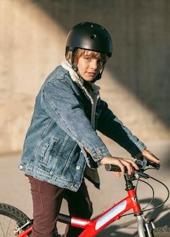 그의 자전거에 포즈를 취하는 안전 헬멧을 가진 소년의 모습